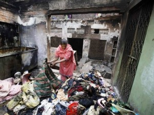 Shumaila, 48, looks through her family belongings at a section of her home, after it was burnt by a mob two days earlier, in Badami Bagh. PHOTO: REUTERS