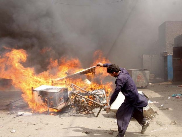 A Deobandi militant of ASWJ burns belongings from Christian houses in Lahore on Saturday.