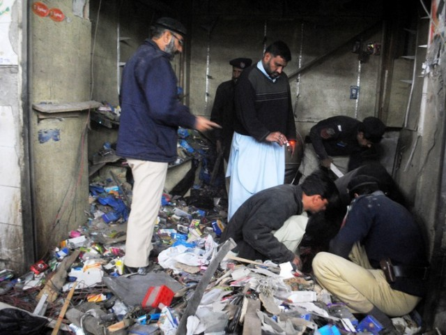 Police carry out investigations after a bomb blast in Peshawar. PHOTO: Muhammad Iqbal/Express