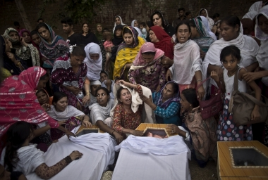 Pakistani women grieve over the coffins of their relatives, who were killed in a suicide attack on a church, in Peshawar, Pakistan, 22 September 2013.