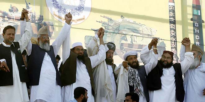 PESHAWAR, PAKISTAN, APR 15: Difa-e-Pakistan Council leaders, Mulana Sami-ul-Haq, Hafiz Mohmmad and other joint hands on stage during Difa-e-Pakistan conference held in Peshawar on Sunday, April 15, 2012. (Fahad Pervez/PPI Images).